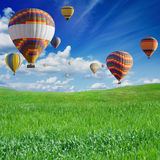 Hot air ballooning above green field Stock Photo
