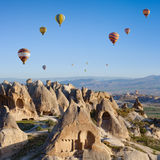 Hot air ballooning in Cappadocia, Turkey. Hand carved rooms in unusual rock formation in Goreme, Cappadocia, Turkey. Hot air ballooning in morning is most stock images