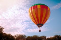 Hot air ballooning. The colorful hot air balloon is flying above trees on cloudy blue sky. Hot air ballooning stock images