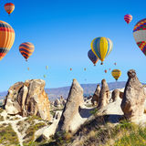 Hot air ballooning in Kapadokya, Turkey. Sunny weather, limestone conical rocks near Goreme, Cappadocia, Turkey. Hot air ballooning is most popular attraction in royalty free stock images