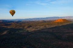Hot air ballooning over sedona Arizona showing balloon and butte. Hot air ballooning over Sedona Arizona showing red mountains and buttes royalty free stock images