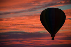 Hot-air ballooning among pink and orange clouds Royalty Free Stock Photography