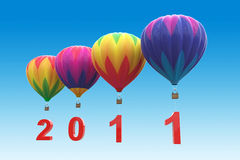Hot air balloons 2011. Colorful hot air balloons with red number 2011 on blue background Royalty Free Stock Photo