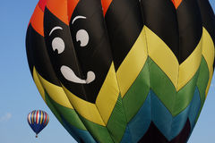 Hot Air Balloons. Two hot air balloons one close and one far, the bigger balloon looks like it wants to eat the smaller balloon royalty free stock image