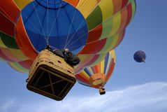 Hot air balloons 3. Two colourful hot air balloons chasing the blue one high in the sky royalty free stock images