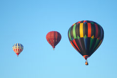 Hot air balloons. In the sky displaying their brilliant colors. Focus point is on larger balloon Stock Images