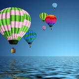 Hot air balloons. Couple of colorful hot air balloons flying over the ocean Stock Photos