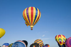 Hot-air balloons ascending over inflating ones. On the ground Royalty Free Stock Photography