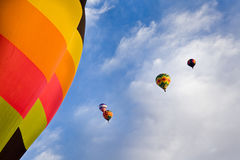 Hot Air Balloons and Blue Sky with Clouds Above New Mexico. Five colorful hot air balloons, one looming in the foreground, float in the painterly morning sky Royalty Free Stock Image