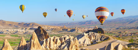 Hot air balloons in Cappadocia, Turkey. Panoramic view of unusual rocky landscape in Cappadocia, Turkey. Hot air ballooning in morning is most amazing attraction Royalty Free Stock Image