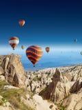 Hot air balloons flies in clear deep blue sky in Cappadocia Stock Photos