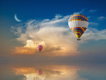 Hot air balloons flies in glowing sunset sky above calm sea Stock Photography