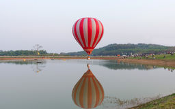 Hot air balloons flight over lake. Royalty Free Stock Image