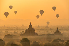 Hot air balloons float over pagodas field