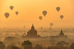 Hot air balloons float over pagodas field Stock Photos