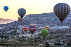 Hot air balloons float through the spectacular landscape around Goreme at sunrise in the Cappadocia region of Turkey. Stock Photos