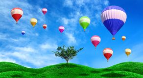 Hot air balloons floating over green field Royalty Free Stock Image