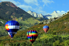 Hot air balloons floating over Rocky Mountains Stock Photos