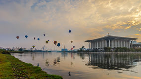 Hot air balloons floating over sunrise at Putrajaya. Royalty Free Stock Photo