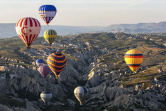 Hot air balloons fly over the beautiful landscape near Goreme in the Cappadocia region of Turkey. Stock Image