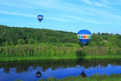 Hot air balloons. Fly on the hot air balloons over the river Royalty Free Stock Photo