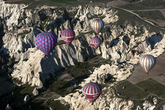 Hot air balloons fly over the spectacular Goreme landscape in the Cappadocia region of Turkey. Stock Images
