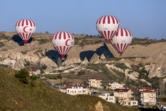 Hot air balloons fly over a village at sunrise near Goreme in the Cappadocia region of Turkey. Royalty Free Stock Photo