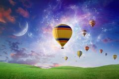Hot air balloons fly in sunset sky against background of glowing Royalty Free Stock Photography