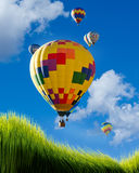 Hot Air Balloons. Hot air balloons flying high over green grass Royalty Free Stock Photo