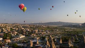 Hot air balloons flying over Goreme at sunrise with sandstone formations in the foreground royalty free stock image