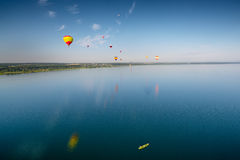 Hot air balloons flying over lake. Stock Photo