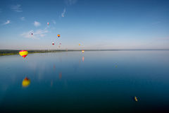 Hot air balloons flying over lake. Stock Image