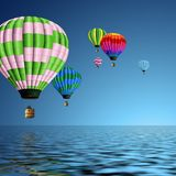 Hot air balloons flying over the ocean. A group  of colorful hot air balloons flying over the ocean Stock Image