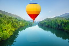 Hot air balloons flying over river Royalty Free Stock Photo