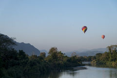 Hot air balloons flying over the river Nam Song at sunrise. Vang Vieng, Laos Stock Photos