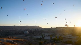 Hot air balloons flying over valley at sunrise. Cappadocia. Turkey stock footage
