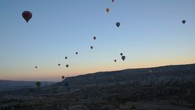 Hot air balloons flying over valley at sunrise. Cappadocia. Turkey stock video