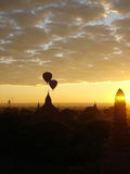 Hot air balloons flying through sunrise scene over Bagan temple complex Royalty Free Stock Images