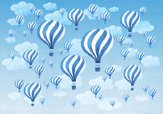 Hot air balloons flying throught a cloudy blue sky Stock Images