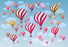 Hot air balloons flying throught a cloudy blue sky Stock Photo