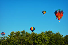 Hot Air Balloons. Four rainbow hot air balloons floating above the trees at the Waterford, Wisconsin balloon festival Royalty Free Stock Images