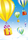 Hot air balloons with gift boxes. Several colorful hot air balloons are carrying bright gift boxes in the blue sky with white clouds Stock Photography