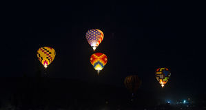 Hot-Air Balloons. Hot air balloons glowing in the night Stock Image