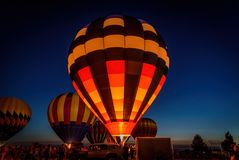 Hot air balloons glowing in night sky Stock Photo