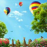 Hot air balloons high in the blue sky, view from house garden Royalty Free Stock Photos