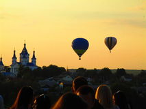Hot air balloons, Kamenets Podolskiy, Ukraine. Silhouette of some balloons on the background of a church and the old town at sunset Royalty Free Stock Image