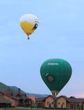 Hot air balloons landing on courtyards. Campu Cetatii, Mures, Romania - September 29, 2012: Couple of hot air balloons landing on some houses in Campu Cetatii Stock Image