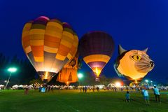Hot air balloons light up on the field with people walking aroun Stock Photo