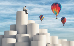 Hot air balloons. Man sitting on top of cylinders using a laptop while hot air balloons flying arround the sky. This is a 3d render illustration Royalty Free Stock Image