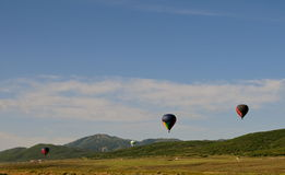 Hot air balloons in the mountains. 4 hot air balloons in the air with a ski resort in the background Stock Photo